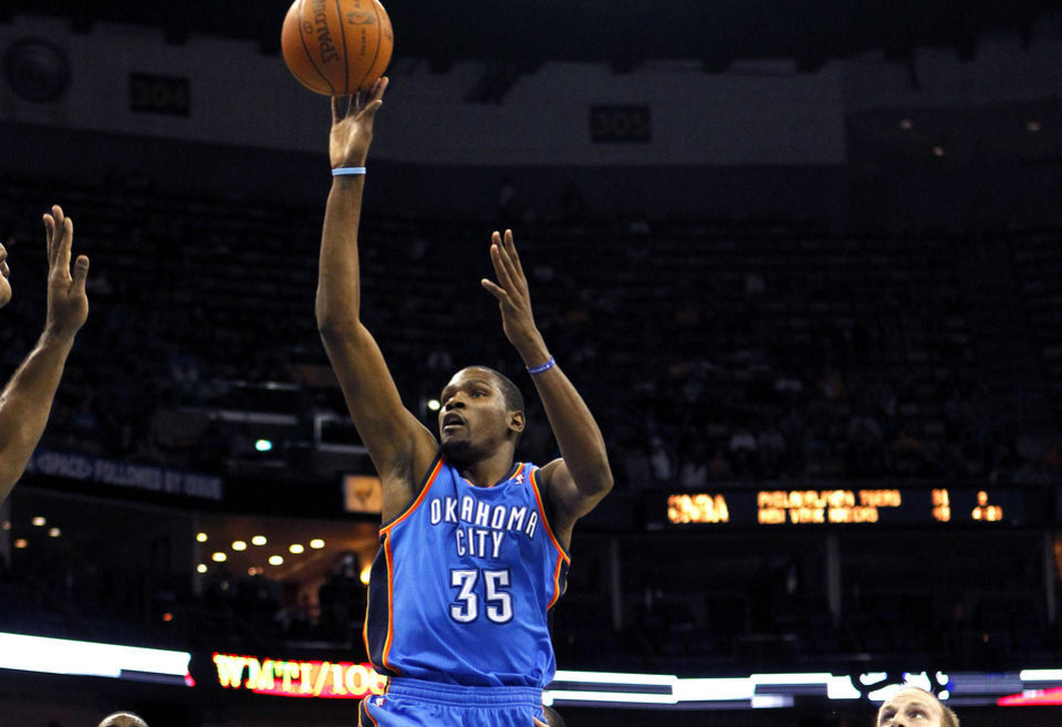 Photo - Oklahoma City Thunder small forward Kevin Durant (35) drives to the basket past New Orleans Hornets small forward Al-Farouq Aminu (0) and center Chris Kaman (35) in the first half of an NBA basketball game in New Orleans, Wednesday, Jan. 11, 2012. (AP Photo/Gerald Herbert)