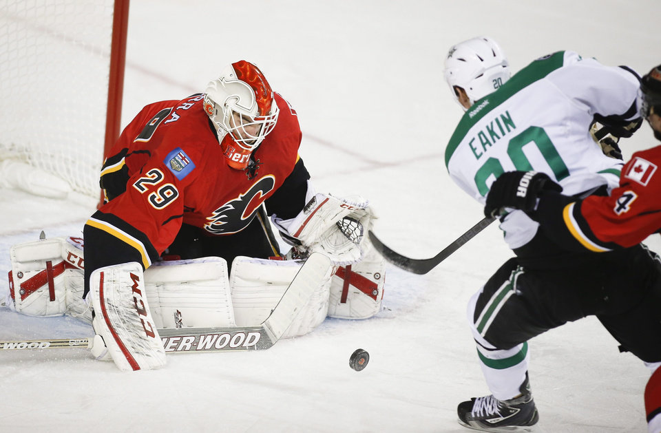 Photo - Dallas Stars' Cody Eakin, right, tries to get the puck past Calgary Flames goalie Reto Berra, from Switzerland, during second-period NHL hockey game action in Calgary, Alberta, Thursday, Nov. 14, 2013. (AP Photo/The Canadian Press, Jeff McIntosh)
