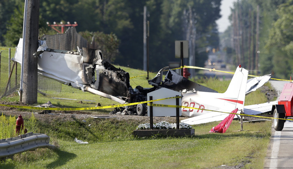 Photo - The wreckage from a plane that crashed rests on the side of a road, Tuesday, Aug. 26, 2014, in Richmond Heights, Ohio. The Cessna 172R crashed and burst into flames just after takeoff Monday from Cuyahoga County Airport in Richmond Heights, Ohio, outside of Cleveland, killing all four people on board, according to the Ohio State Highway Patrol. (AP Photo/Tony Dejak)