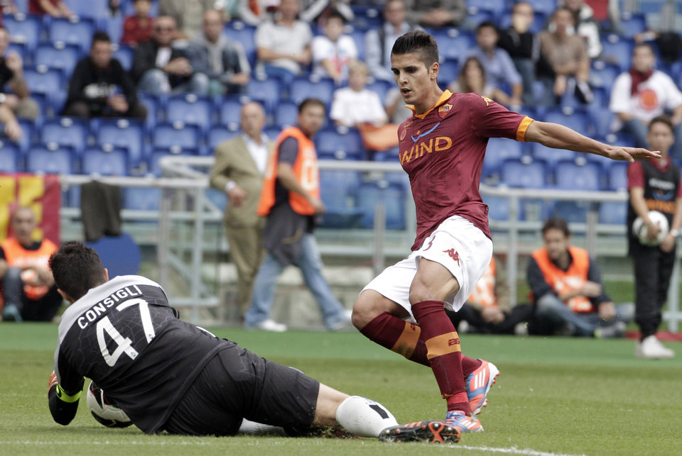 Atalanta goalkeeper Andrea Consigli, on the ground, grabs the ball as AS Roma forward Erik Lamela, of Argentina, challenges him during a Serie A soccer match between AS Roma and Atalanta, at Rome's Olympic stadium, Sunday, Oct. 7, 2012. (AP Photo/Riccardo De Luca)