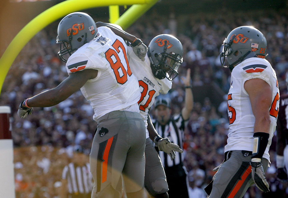 Oklahoma State's Tracy Moore (87), Justin Blackmon (81) and Josh Cooper (25) celebrate a touchdown in the second of the Cowboys 30-29 win over Texas A&M on Saturday in College Station, Texas. Photo by Sarah Phipps, The Oklahoman