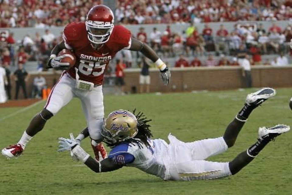 Oklahoma's Ryan Broyles (85) his hit by Tulsa's Milton Howell (19) during the college football game between the University of Oklahoma Sooners ( OU) and the Tulsa University Hurricanes (TU) at the Gaylord Family-Memorial Stadium on Saturday, Sept. 3, 2011, in Norman, Okla. Photo by Chris Landsberger, The Oklahoman ORG XMIT: KOD