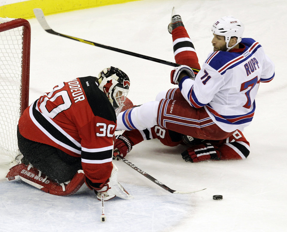 Photo -   New Jersey Devils goalie Martin Brodeur blocks a shot as Anton Volchenkov, of Russia, falls under New York Rangers' Mike Rupp during the first period of Game 4 of an NHL hockey Stanley Cup Eastern Conference final playoff series, Monday, May 21, 2012, in Newark, N.J. (AP Photo/Kathy Willens)