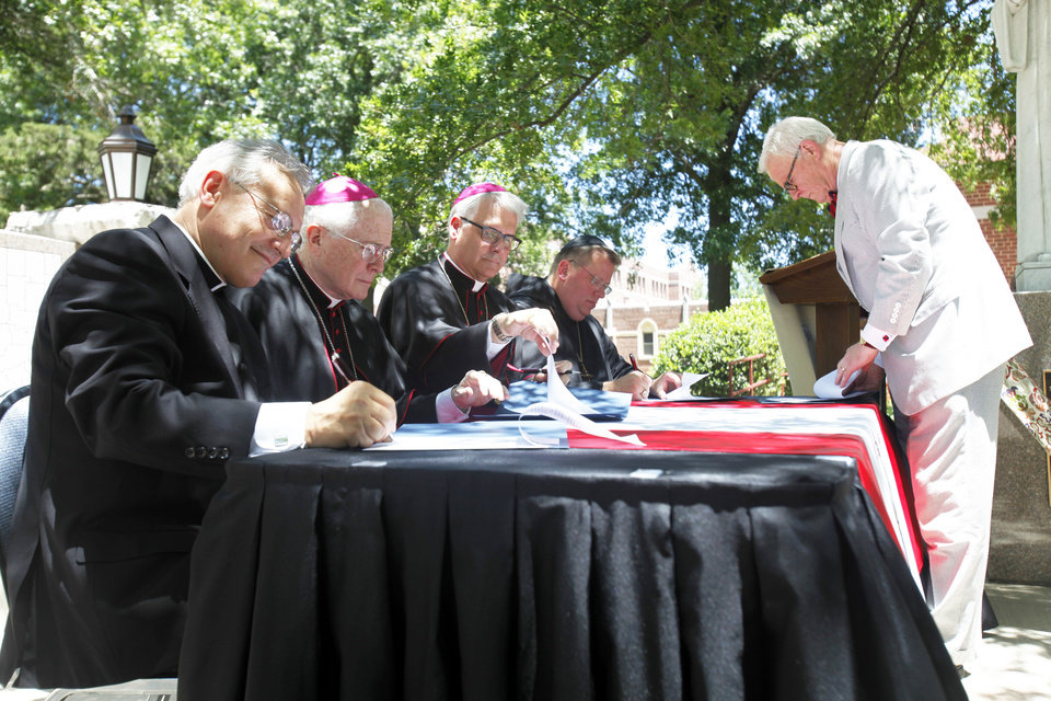 Photo - In a plaza outside St. Gregory's Abbey, St. Gregory's University and Catholic Church leaders in Oklahoma sign a memorandum of agreement Friday, June 28, 2013, establishing the Catholic Church as a major sponsor of the Shawnee university. From left are: the Rev. Don Wolf, St. Gregory's chairman of the board; Tulsa Bishop Edward Slattery; Archbishop of Oklahoma City Paul S. Coakley; and Abbot Lawrence Stasyszen with St. Gregory's, and Greg Main, president of St. Gregory's University.  Aliki Dyer - The Oklahoman