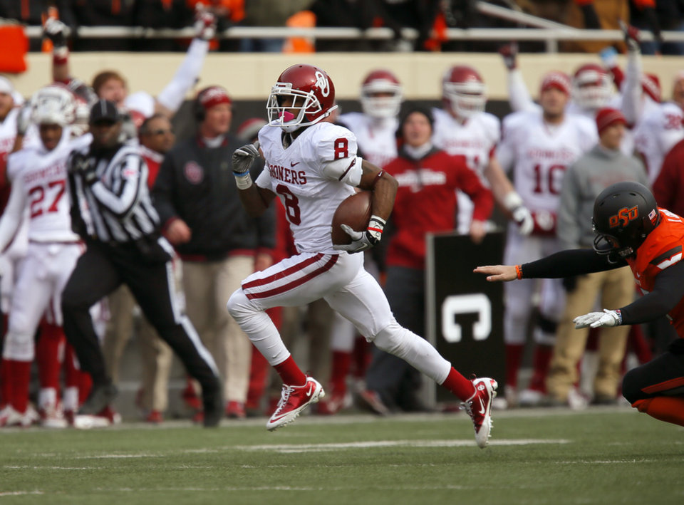 Photo - Oklahoma's Jalen Saunders (8) runs past Oklahoma State's Kip Smith (35) as he returns a punt for a touchdown during the Bedlam college football game between the Oklahoma State University Cowboys (OSU) and the University of Oklahoma Sooners (OU) at Boone Pickens Stadium in Stillwater, Okla., Saturday, Dec. 7, 2013. Photo by Bryan Terry, The Oklahoman