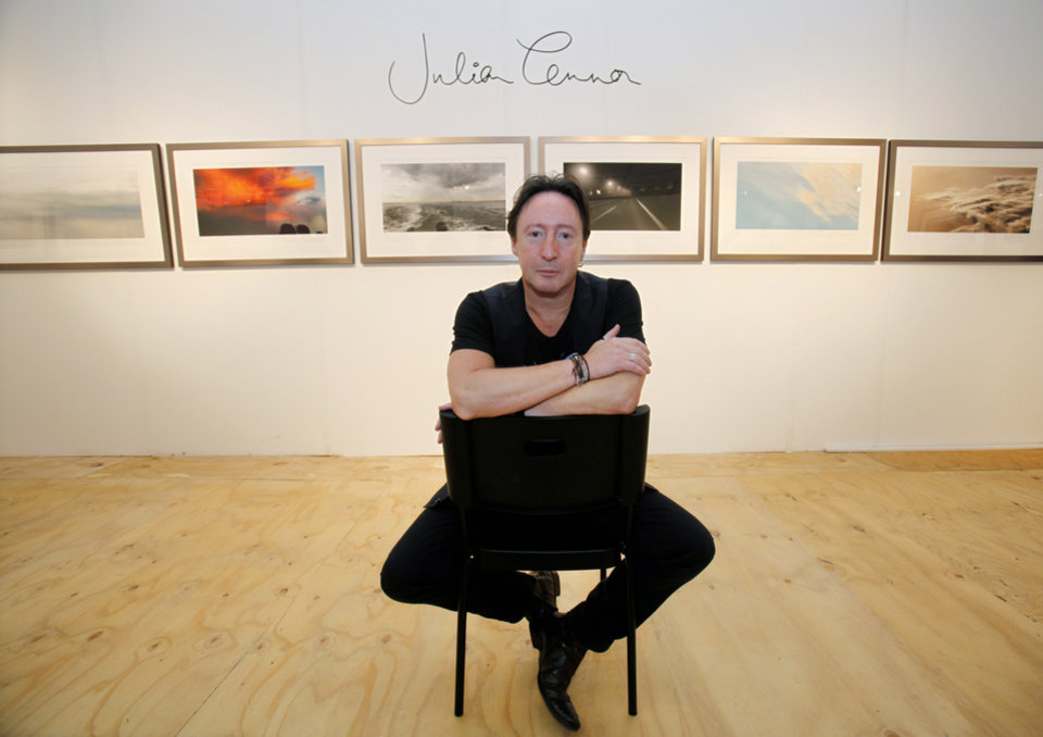 "Photo - Julian Lennon, son of the late Beatles legend John Lennon, poses in front of some of the photographs he is displaying in a show titled ""Alone"" at the Overture Art Fair, Monday, Dec. 3, 2012 in Miami. Art Basel Miami Beach and about two dozen other independent art fairs open Thursday. Tens of thousands of people are expected through Sunday at the fairs throughout Miami and South Beach. Lennon also exhibited his photography during the 2010 art fairs, and he was looking forward to enjoying Miami's social scene. ""You get every kind of character and every kind of style,"" he said. ""I just hope that doesn't detract from the actual work of the artists who've come here."" (AP Photo/Wilfredo Lee)"