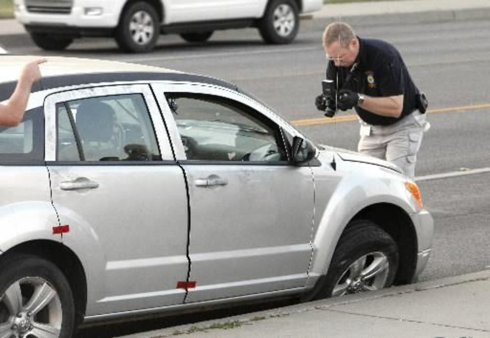 Photo - A Norman Police Department investigator taking photos of a car involved in a Norman shooting that was stopped in south Oklahoma City on May Ave. near SW 67 Street Thursday, Sept. 13, 2012. Photo by Paul B. Southerland