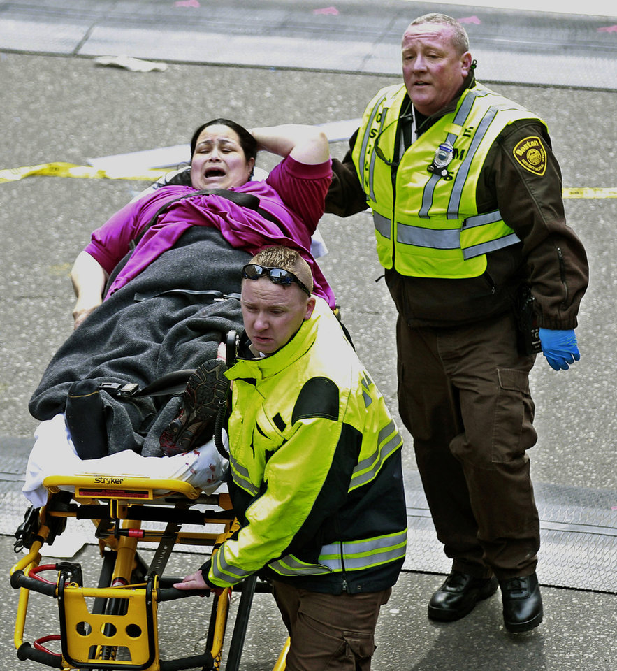 Photo - Medical workers aid an injured woman at the finish line of the 2013 Boston Marathon following two explosions there, Monday, April 15, 2013 in Boston. Two bombs exploded near the finish of the Boston Marathon on Monday, killing at least two people, injuring at least 23 others and sending authorities rushing to aid wounded spectators. (AP Photo/Charles Krupa) ORG XMIT: MACK139