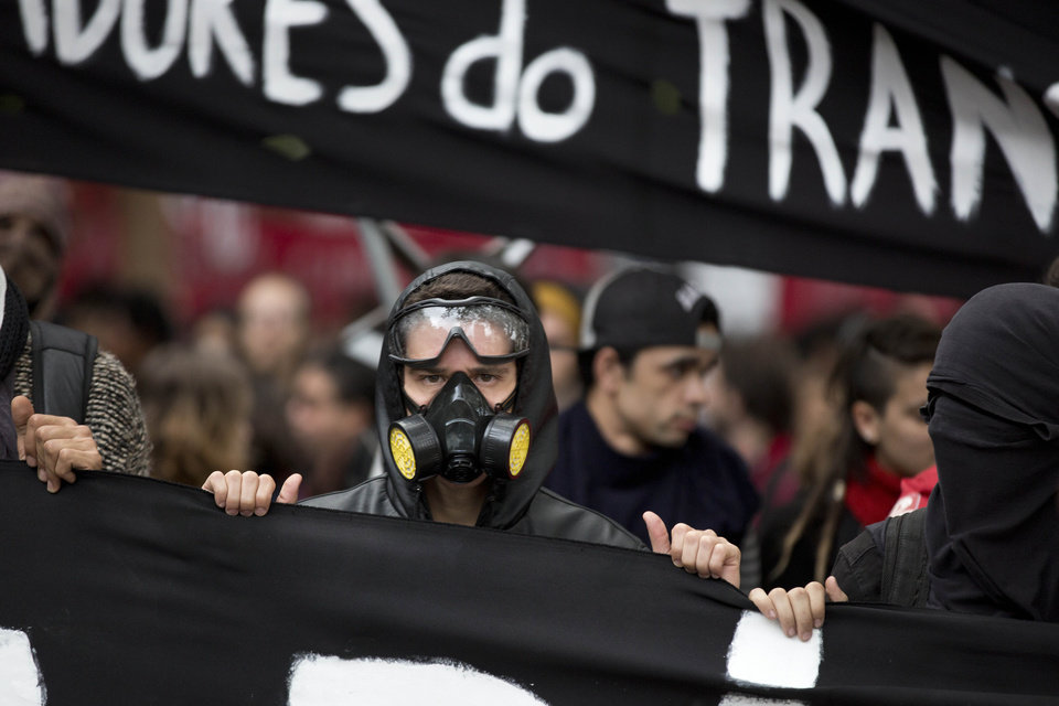 Photo - Masked protesters carry a banner while marching in Sao Paulo, Brazil, Thursday, June 19, 2014. The protest in Sao Paulo, Brazil's biggest city that is hosting a World Cup match,  was called by the Free Fare movement, the group that was behind the first protests last year that sparked roiling anti-government demonstrations across Brazil. (AP Photo/Eduardo Verdugo)
