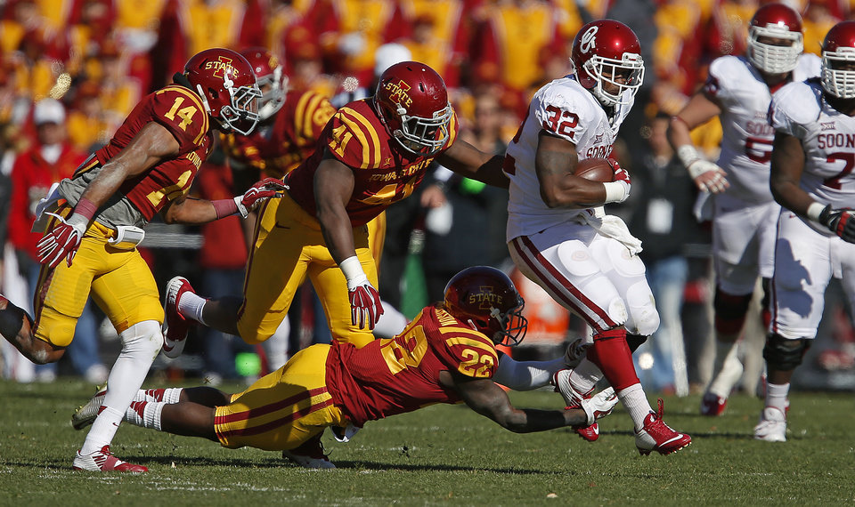 Photo - Oklahoma's Samaje Perine (32) runs past Iowa State's T.J. Mutcherson (22), Darius White (41), and Jared Brackens (14) during a college football game between the University of Oklahoma Sooners (OU) and the Iowa State Cyclones (ISU) at Jack Trice Stadium in Ames, Iowa, Saturday, Nov. 1, 2014. Photo by Bryan Terry, The Oklahoman