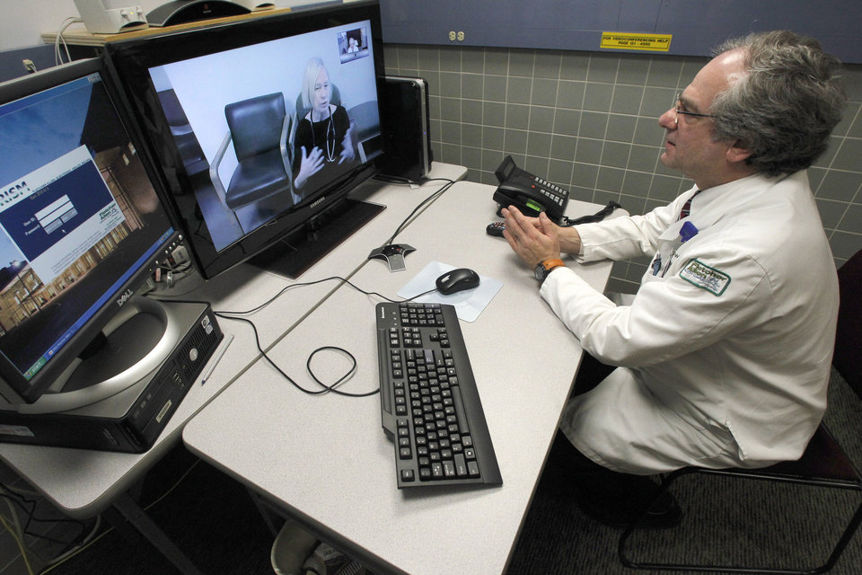 Photo - In this Thursday, Dec. 20, 2012 photo, Dr. Terry Rabinowitz, right, talks with nurse Leslie Orelup at Helen Porter Nursing Home in Burlington, Vt. New health insurance regulations in Vermont are giving a boost to telemedicine, the system that enables health care providers to offer consult with patients without being in the same room. Telemedicine isn't new, but the new regulations make it easier for physicians to be reimbursed for services performed by two-way video hookups. Fletcher Allen Telemedicine director Dr. Terry Rabinowitz says popular specialties are psychiatry and dermatology. (AP Photo/Toby Talbot)