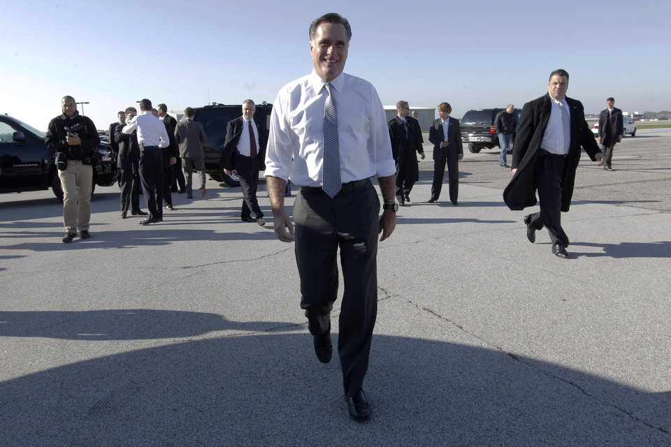 Photo -   Republican presidential candidate, former Massachusetts Gov. Mitt Romney walks toward members of the press after arriving at Cleveland Hopkins International Airport, Tuesday, Nov. 6, 2012, in Cleveland, Ohio. (AP Photo/Mary Altaffer)