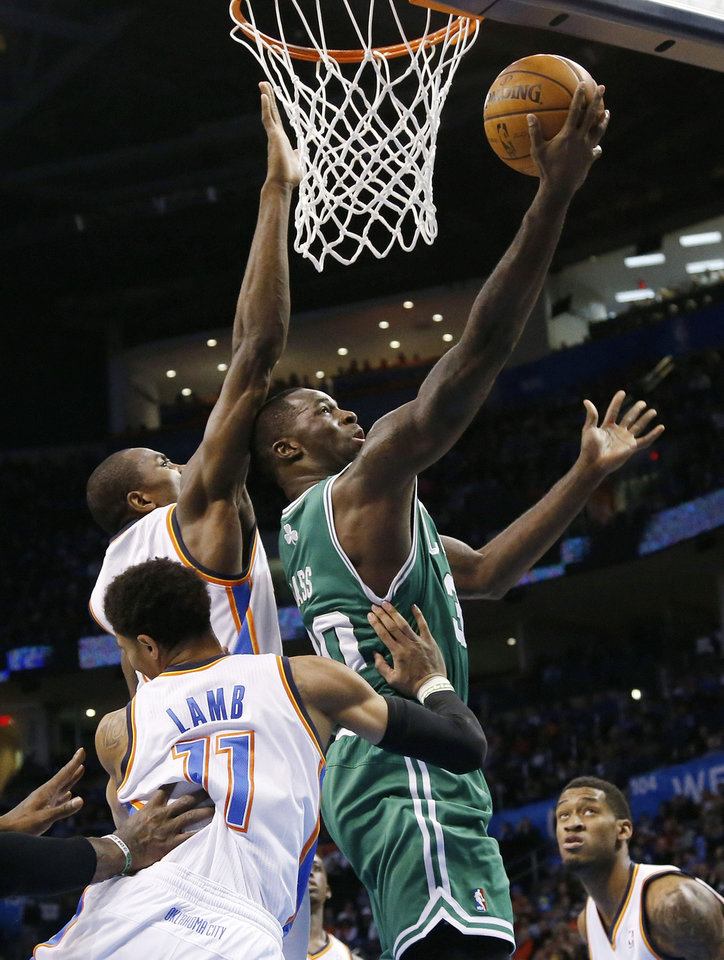 Photo - Boston Celtics forward Brandon Bass, right, shoots in front of Oklahoma City Thunder forward Serge Ibaka and guard Jeremy Lamb (11) in the first quarter of an NBA basketball game in Oklahoma City, Sunday, Jan. 5, 2014. (AP Photo/Sue Ogrocki)