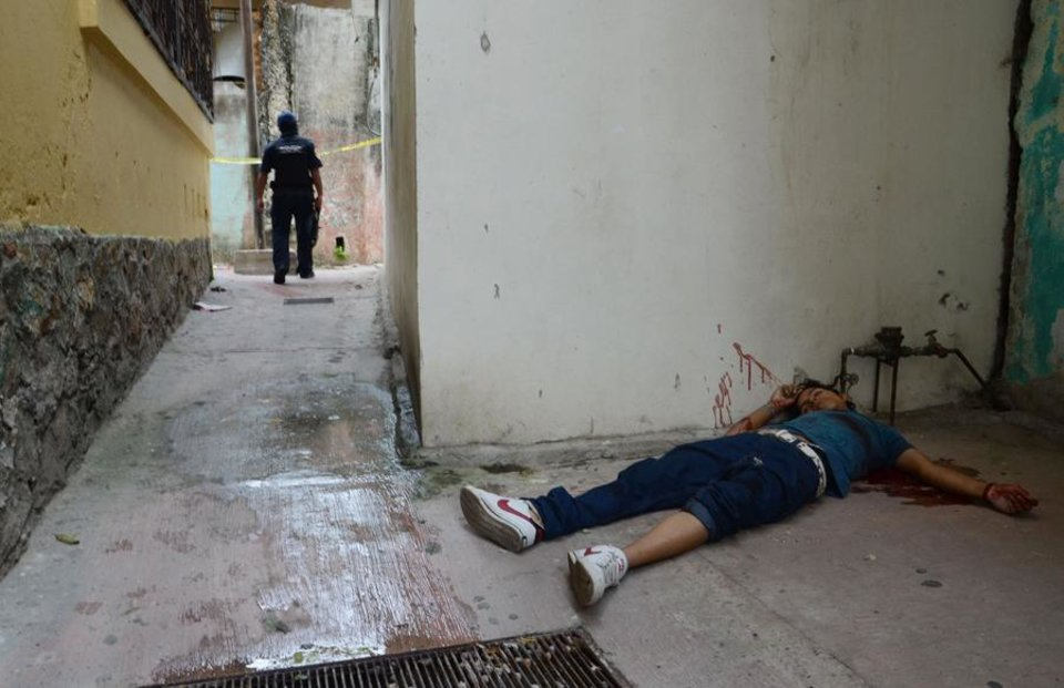 Photo -  The body of a young man who was shot to death lies on the ground at the Pacific resort city of Acapulco, Mexico, Tuesday Aug. 23, 2011. The city of Acapulco has been hit by violence as drug gangs continue to battle for control of the region. (AP Photo/Bernandino Hernandez)