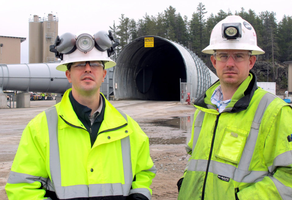 Photo - In this May 8, 2014 photo Eagle Mine advisors Dan Blondeau, left, and Andy Vaughn stand outside the mine's portal in Marquette, Mich. It's managers say the mine, a nickel and copper operation scheduled to begin production this fall, will pump $4 billion into Marquette County over its eight-year lifespan and employ about 300 while generating economic activity that will create 1,200 additional jobs. (AP Photo/John Flesher)