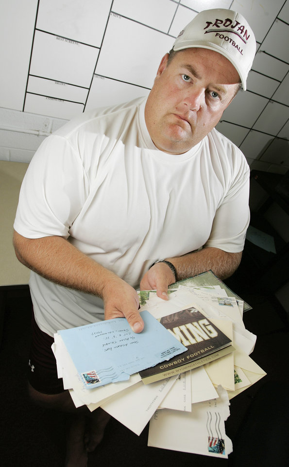 Photo - SUV: Jenks High School football head coach Allan Trimble holds some of the many letters of support he received after the death of Trojans player Garrett Bennett, at Jenks High School in Jenks, Okla., Tuesday, September 5, 2006. Bennett was killed July 12, 2006, when a sports utility vehicle driven by a teammate went off the road and flipped over after a paintball shoot-out on the Creek Turnpike. By Nate Billings, The Oklahoman ORG XMIT: KOD