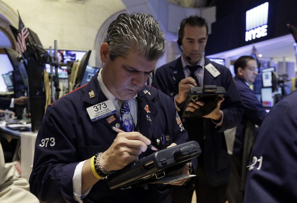 Photo - Trader John Panin, left, works on the floor of the New York Stock Exchange Wednesday, July 9, 2014.  Stocks inched higher in early trading Wednesday, reversing a two-day decline, as the quarterly earnings season got underway with some positive news from the giant aluminum company Alcoa. (AP Photo/Richard Drew)