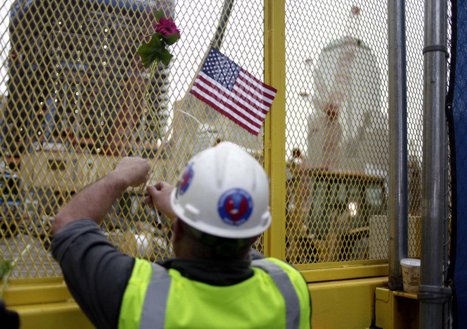 Photo - Construction worker Paddy Garvey affixes an American flag to a fence at ground zero in New York, Monday, May 2, 2011. Osama bin Laden, the face of global terrorism and architect of the Sept. 11, 2001, attacks, was killed in a firefight with elite American forces in Pakistan on Monday, May 2, 2011 then quickly buried at sea. (AP Photo/Seth Wenig)