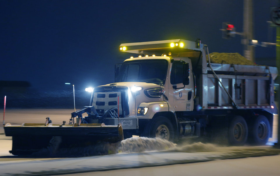 Photo - A city plow removes snow from an intersection along 6th Street in Lawrence, Kan., Sunday, March 2, 2014. (AP Photo/Orlin Wagner)