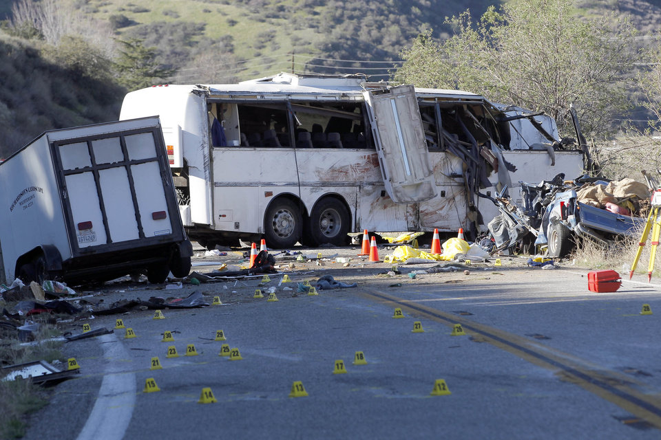 Evidence markers dot the road in front of the wreckage of a tour bus in the Southern California mountains near San Bernardino Monday Feb. 4, 2013.  The tour bus carrying dozens of men, women and children from Tijuana, Mexico, crashed killing at least eight people, authorities said. ( AP Photo/Nick Ut)