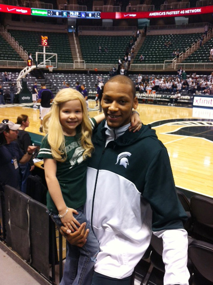 Photo - In this photo provided by Matt Holsworth, Michigan State's Adreian Payne holds Lacey Holsworth, 7, at the Breslin Center in East Lansing, Mich., on March 10, 2013. Payne may be a pivotal player when third-seeded Michigan State faces second-seeded Duke on Friday night in Indianapolis. His improved play has been impressive and yet it pales in comparison to his off-the-court story since he has befriended a 7-year-old girl during her bout with cancer. (AP Photo/Matt Holsworth)