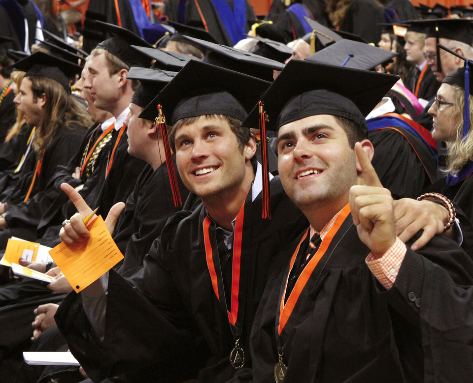 """Garrett Easterling, left, from Richardson, TX, and friend Tyler McClure, from Turpin, OK, show the """"Go Pokes"""" sign with their hands as they pose for a picture taken by someone in the upper seating level. Undergraduates at OSU participated in the school's 127th commencement ceremony the weekend of Friday, May 3 and Saturday, May 4, 2013 inside Gallagher-Iba Arena on the university's campus.These photos were taken at the Saturday morning ceremony when students from the College of Agricultural Sciences and Natural Resources, and the Spears School of Business were conferred with degrees.   Photo  by Jim Beckel, The Oklahoman."""