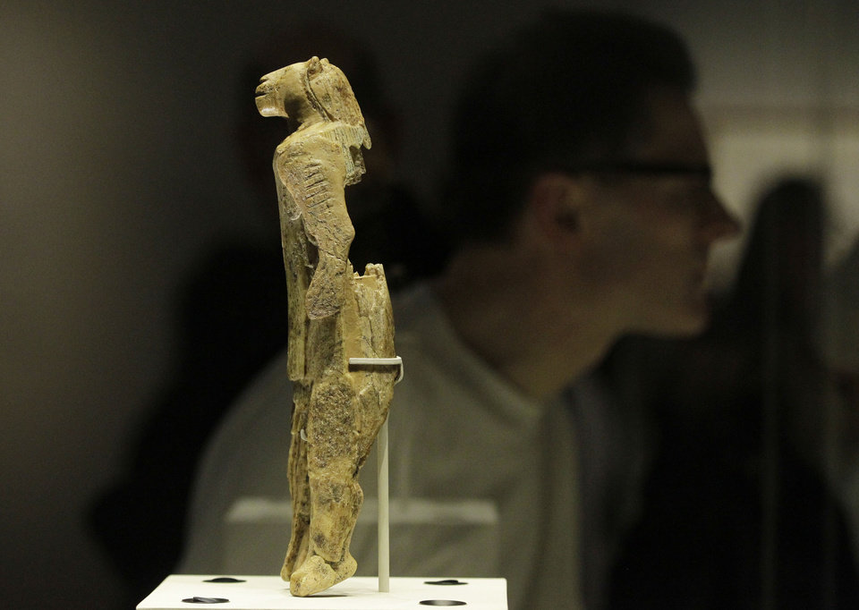 Photo - A mammoth ivory sculpture depicts a man with a lion's head, discovered at Stadel Cave, Baden-Wurttemberg, Germany, dates to around 40,000 years ago is seen on display in an exhibition 'Ice Age Art : arrival of the modern mind' at the British Museum in London, Tuesday, Feb. 5, 2013. The exhibition present masterpieces create from the last Ice Age between 40,000 and 10,000 years ago, drawn from across Europe, by artists with modern minds and presented alongside modern works  to illustrate the fundamental human desire to communicate and make art as a way of understanding ourselves and our place in the world. (AP Photo/Sang Tan)