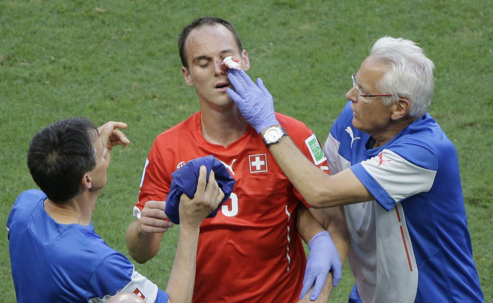 Photo - Switzerland's Steve von Bergen, centre, gets treatment after being injured during the group E World Cup soccer match between Switzerland and France at the Arena Fonte Nova in Salvador, Brazil, Friday, June 20, 2014. (AP Photo/Sergei Grits)