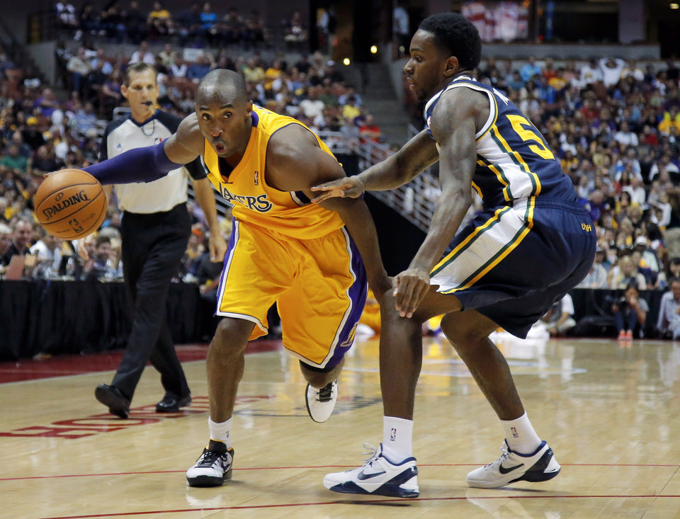 Photo -   Los Angeles Lakers' Kobe Bryant, left, is pressured by Utah Jazz's Kevin Murphy during the first half of an NBA preseason basketball game in Anaheim, Calif., Tuesday, Oct. 16, 2012. (AP Photo/Jae Hong)