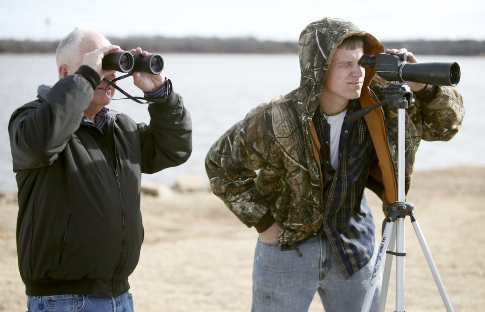 David Kirkegard (left) and Nick Garrett look at an eagle over a mile away during the annual Eagle Watch at Lake Arcadia in Edmond, OK, Friday, Jan. 7, 2011. By Paul Hellstern, The Oklahoman