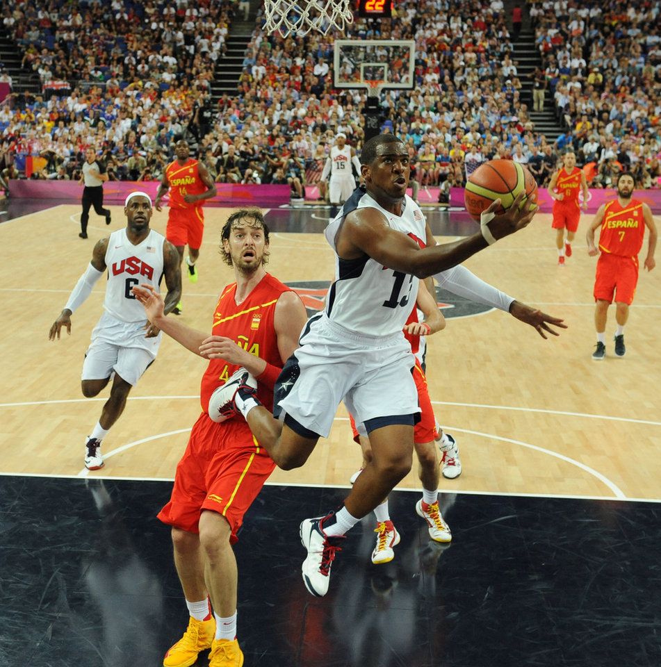 United States' guard Chris Paul, right, jumps to score over Spain's forward Pau Gasol during the men's gold medal basketball game at the 2012 Summer Olympics  in London on Sunday, Aug. 12, 2012. (AP Photo/Mark Ralston, Pool)