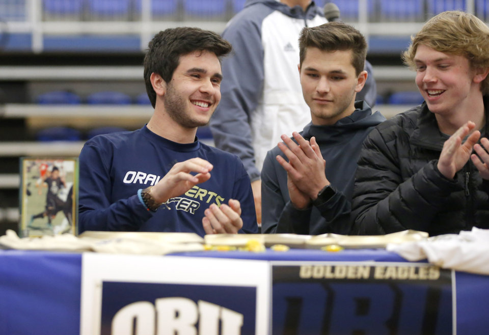 Photo - Deer Creek soccer player Chris Smirlis, left, smiles after signing a letter of intent to play soccer at Oral Roberts University as his friends, Carter Noble, center, and Matthew Loftis listen during a signing day ceremony at Deer Creek High School, Wednesday, Feb. 7, 2018.  Photo by Bryan Terry, The Oklahoman
