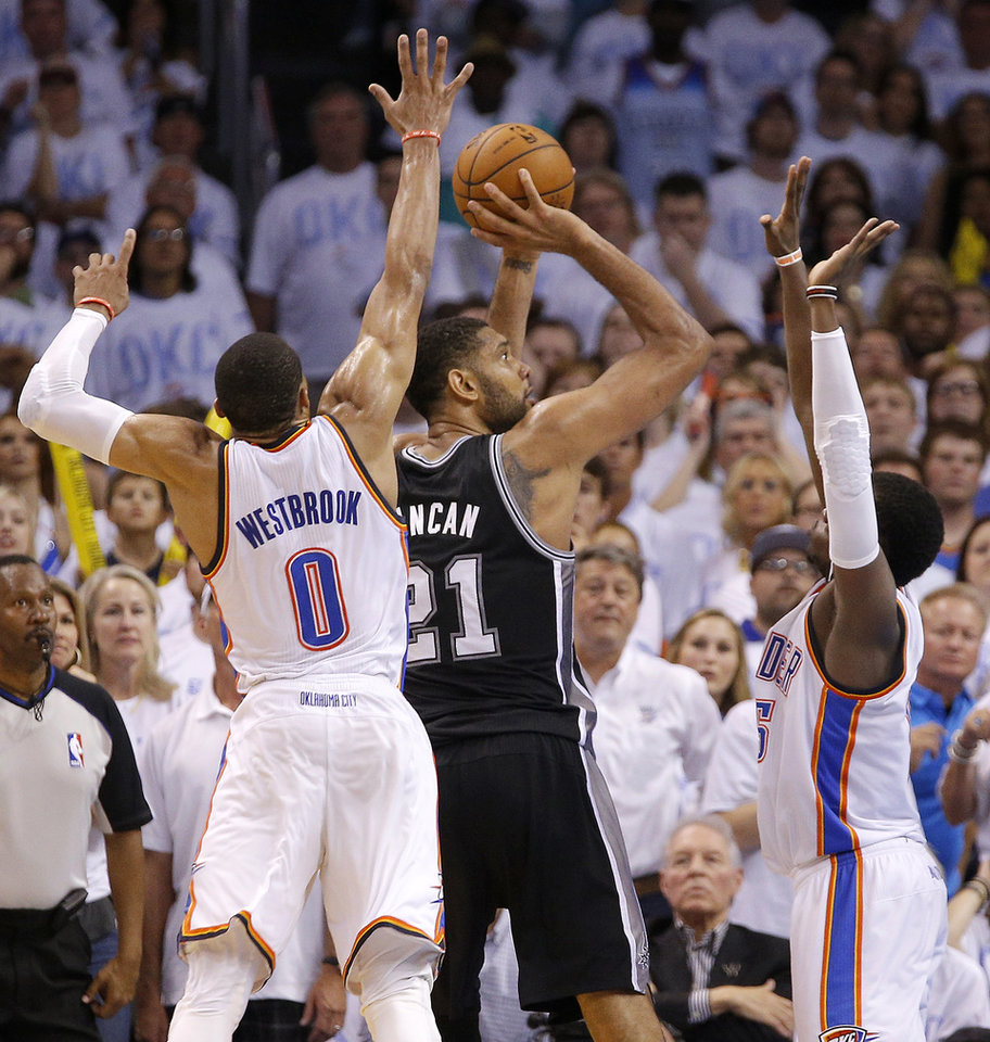 Photo - San Antonio's Tim Duncan (21) hits a shot late in overtime from between Oklahoma City's Russell Westbrook (0) and Reggie Jackson (15) during Game 6 of the Western Conference Finals in the NBA playoffs between the Oklahoma City Thunder and the San Antonio Spurs at Chesapeake Energy Arena in Oklahoma City, Saturday, May 31, 2014. Oklahoma City lost 112-107. Photo by Bryan Terry, The Oklahoman