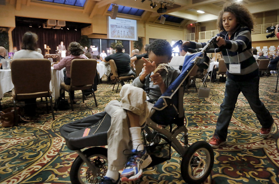 Photo - Tobias Bass, right, walks with this brother Titus as they prepare to be presented with the Special Award Tuesday during the 23rd annual Mayor's Committee on Disability Concerns awards at St. Luke's United Methodist Church in Oklahoma City. Photo by Chris Landsberger, The Oklahoman  CHRIS LANDSBERGER