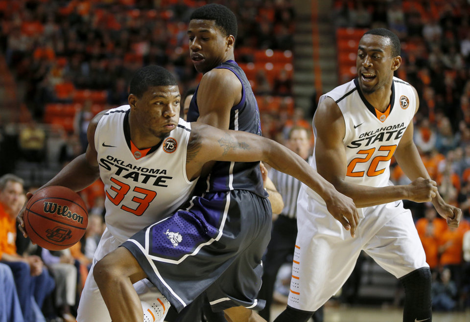 Photo - Oklahoma State's Marcus Smart (33) goes around TCU's Brandon Parrish (11) as Markel Brown (22) watches during an NCAA college basketball game between Oklahoma State University (OSU) and TCU at Gallagher-Iba Arena in Stillwater, Okla., Wednesday, Jan. 15, 2014. Oklahoma State won 82-50. Photo by Bryan Terry, The Oklahoman