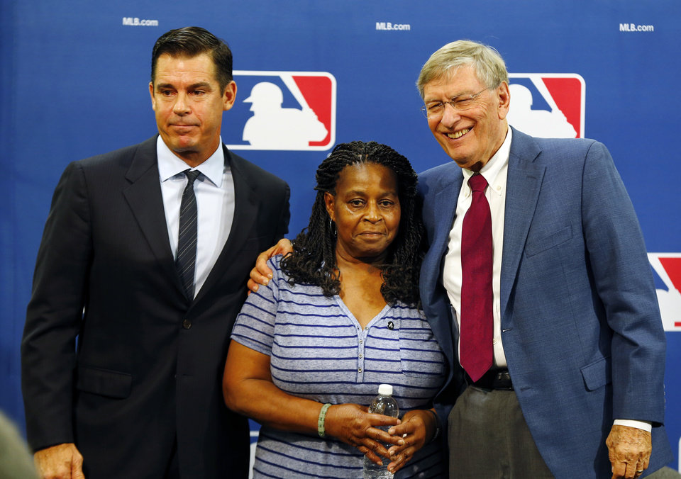Photo - Former major league outfielder Billy Bean, left, Lutha Burke and Baseball Commissioner Bud Selig, right, pose for a photo after a news conference at baseball's All-Star game, Tuesday, July 15, 2014, in Minneapolis. Major League Baseball has appointed Bean, who came out as gay after his playing career, to serve as a consultant in guiding the sport toward greater inclusion and equality. Burke is the sister of Glenn Burke, who was the first MLB player to come out as gay after retiring. Burke died in 1995. (AP Photo/Paul Sancya)