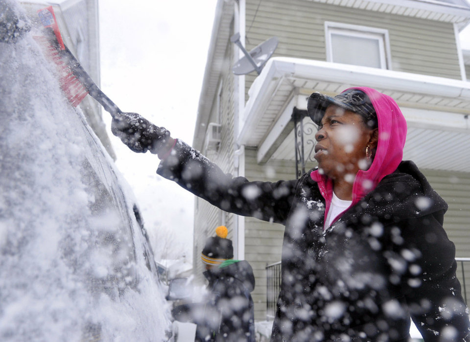 Ice and snow fliy as Cornelia Beard, right, and her son Keshaun Beard, 8, background left, both of Erie, Pa., clear snow off of their car at home in Erie on Dec. 27, 2012 following a snow storm that dumped nine inches of snow on the Erie region, according to the National Weather Service. (AP Photo/Erie Times-News, Andy Colwell)  TV OUT; MAGS OUT; COMMERCIAL INTERNET OUT