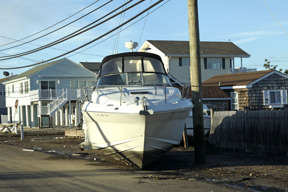 A boat washed inland by superstorm Sandy sits on the road in Ship Bottom on Long Beach Island, N.J. on Thursday, Nov. 1, 2012. New Jersey got the brunt of supersrtorm Sandy, the storm that made landfall Monday, caused multiple fatalities, halted mass transit and cut power to more than 6 million homes and businesses. (AP Photo/Robert Ray)