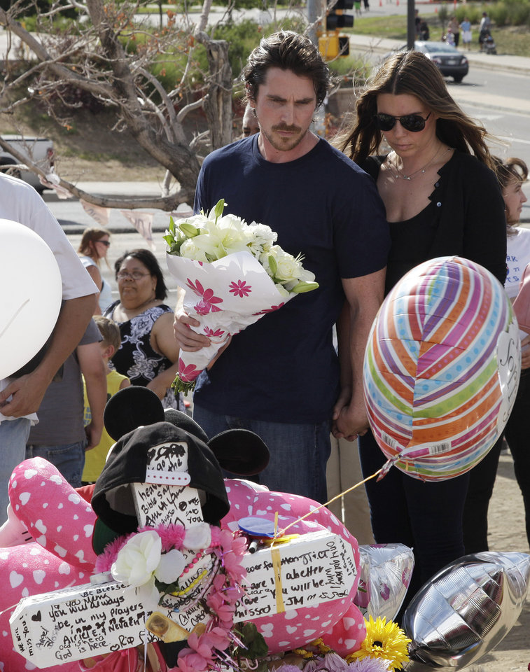 Photo -   Actor Christian Bale and his wife Sibi Blazic carry flowers as they visit a memorial to the victims of Friday's mass shooting, Tuesday, July 24, 2012, in Aurora, Colo. Twelve people were killed when a gunman opened fire during a late-night showing of the movie