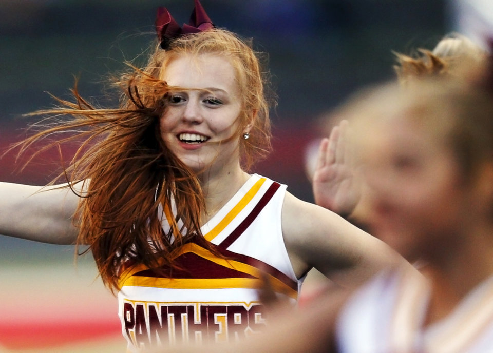 Strong winds blow the hair of Putnam City North cheerleader Sasha Logoutine, a junior, as she cheers with the rest of the squad during a high school football game between Mustang and Putnam City North in Mustang, Okla., Friday, Sept. 7, 2012. Photo by Nate Billings, The Oklahoman