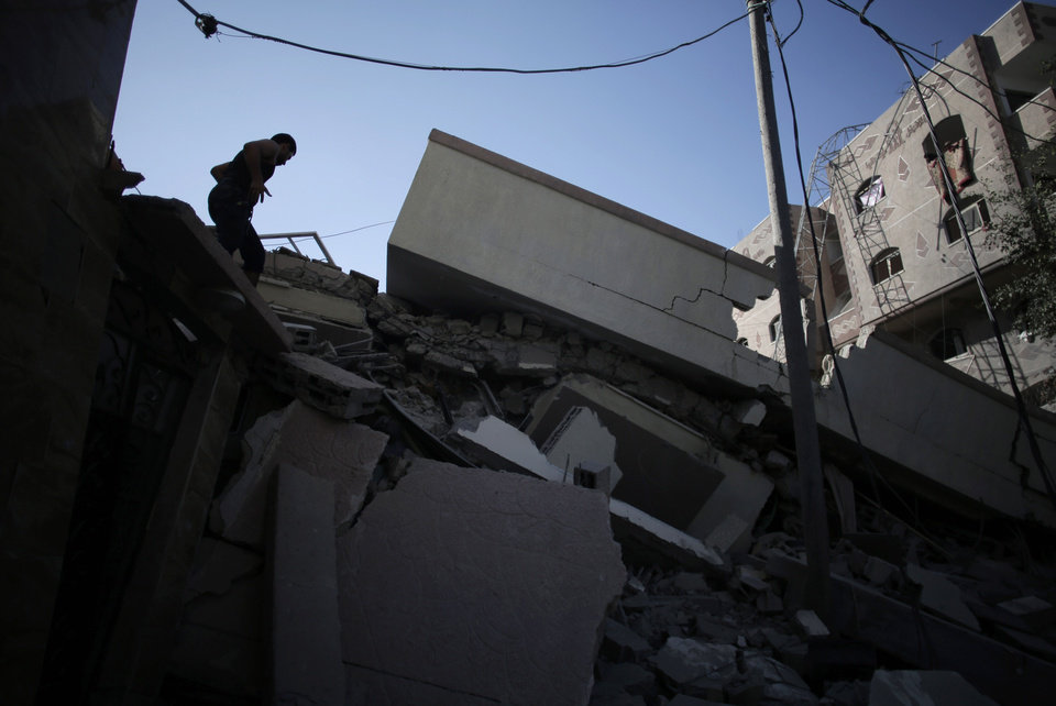 Photo - A Palestinian man inspects the damage of a destroyed house following an overnight Israeli strike in Gaza City Friday, July 25, 2014. Early Friday, Israeli warplanes struck tens of houses throughout the Gaza Strip as international efforts continue to broker a cease fire in the 18 day-old war. (AP Photo/Khalil Hamra)