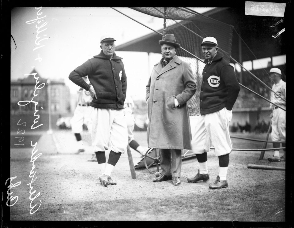 Photo - This 1922 photo provided by the Chicago History Museum shows from left, Chicago Cubs baseball player Pete Alexander, team owner William Wrigley Jr., and manager Bill Killefer standing behind a batting practice backstop on the field at Weeghman Park, in Chicago. Weeghman Park was renamed Wrigley Field in 1927. The famed ballpark will celebrate it's 100th anniversary on April 23, 2014. (AP Photo/Courtesy of the Chicago History Museum)
