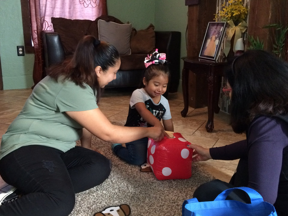 Photo -  Morenia Martinez and her daughter, Alexa, 3, practice counting with a game on Nov. 2 at their Oklahoma City home. Consuelo Rozo, right, is a parent educator in the Parents as Teachers program at the Latino Community Development Agency. Rozo works with the Martinezes and other families to improve how they relate to their children, with the goal of improving children's development and reducing their risk of abuse or neglect. The program is scheduled to end because of cuts by the Oklahoma State Department of Health. [Photo by Meg Wingerter, The Oklahoman]