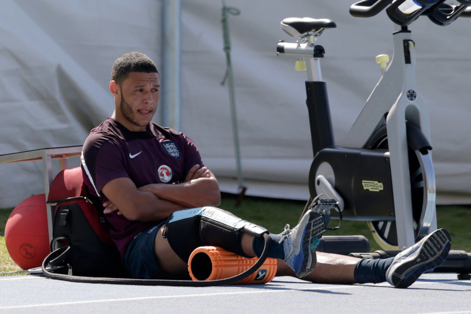 Photo - England's Alex Oxlade-Chamberlain sits down after performing some running exercises whilst training away from the rest of the squad as he continues to recover from a knee injury during a squad training session for the 2014 soccer World Cup at the Urca military base in Rio de Janeiro, Brazil, Monday, June 9, 2014.  (AP Photo/Matt Dunham)