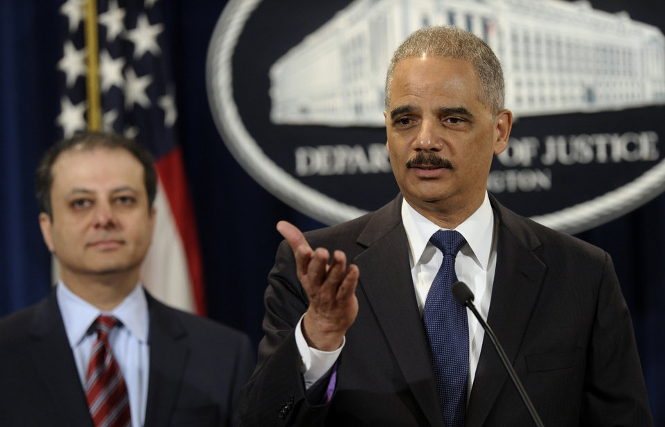 Photo - Attorney General Eric Holder, right, accompanied by U.S. Attorney for the Second District Preet Bharara, announces a $1.2 billion settlement with Toyota over its disclosure of safety problems, Wednesday, March 19, 2014, during a news conference at the Justice Department in Washington. (AP Photo/Susan Walsh)