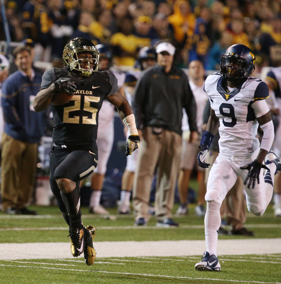 Photo - Baylor running back Lache Seastrunk (25) scores past West Virginia safety K.J. Dillon (9), right, during the first half of an NCAA college football game on Saturday, Oct.  5, 2013, in Waco, Texas. (AP Photo/Rod Aydelotte)