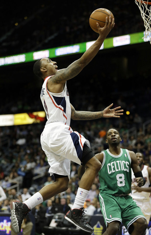 Photo - Atlanta Hawks' Jeff Teague, left, puts up a shot in front of Boston Celtics' Jeff Green in the first quarter of an NBA basketball game, Wednesday, April 9, 2014, in Atlanta. The Hawks won 105-97. (AP Photo/David Goldman)
