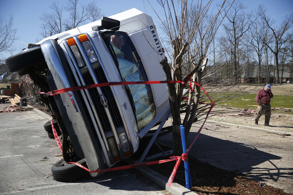 Photo - Eldon Pipkin, owner of an over turned truck,  talks on the phone with insurance agents, Wednesday, March 2, 2016, after damage from storms that struck Tuesday evening in Bessemer, Ala.  Forecasters say a tornado that severely damaged homes and trees in the Birmingham suburb has been determined as an EF2, with winds of between 120 and 125 mph.  (AP Photo/Brynn Anderson)