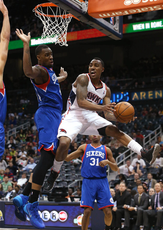 Photo - Atlanta Hawks guard Jeff Teague, right, looks to pass under the defense of Philadelphia 76ers forward Jarvis Varnado in the first half of an NBA basketball game Monday, March 31, 2014, in Atlanta. (AP Photo/Jason Getz)