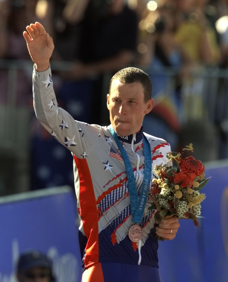 FILE - In a Sept. 30, 2000 file photo, U.S. cyclist Lance Armstrong waves after receiving the bronze medal in the men\'s individual time trials at the 2000 Summer Olympics cycling road course in Sydney, Australia. Officials familiar with the decision tell The Associated Press the IOC has stripped Armstrong of his bronze medal from the 2000 Sydney Olympics because of his involvement in doping. Two officials say the IOC sent a letter to Armstrong on Wednesday night, Jan. 16, 2013, asking him to return the medal. (AP Photo/Ricardo Mazalan, File)